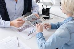 Geschäftsleute, die Bericht im Büro besprechen lizenzfreies stockbild