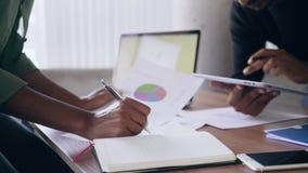 Geschäftsleute, die Daten in der Chefetage im Büro analysieren stock footage