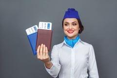 Geschäftsleute, die an dem harten Job arbeiten Stewardessstellung lokalisiert auf Grau mit Pässen und dem Kartennahaufnahmelächel stockbilder