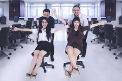 Geschäftsleute, die den Spaß läuft auf Bürostühlen haben lizenzfreies stockbild