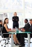 Geschäftsleute, die an der Kamera in einer Sitzung lächeln stockfotografie
