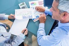 Geschäftsleute, die Dokumente mit Grafiken betrachten Stockfotos