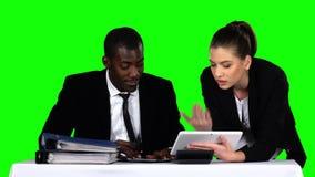 Geschäftsleute, die ein Dokument in ihrem Büro mit einem Laptop überprüfen stock footage