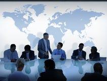 Geschäftsleute, die eine Diskussion und eine Weltkarte haben Lizenzfreie Stockfotografie