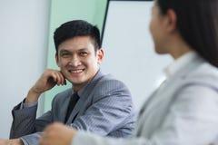 Geschäftsleute, die in einem Konferenzsaal sprechen Lizenzfreies Stockfoto