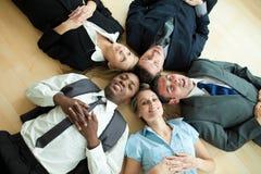 Geschäftsleute, die in einem Kreis auf dem Fußboden liegen lizenzfreies stockbild