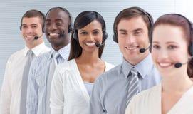 Geschäftsleute, die in einem Kundenkontaktcenter in einer Zeile arbeiten Stockbilder