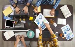 Geschäftsleute, die an einem Schreibtisch arbeiten Lizenzfreie Stockbilder