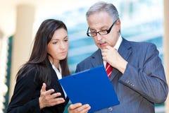 Geschäftsleute, die einige Dokumente lesen lizenzfreie stockfotografie
