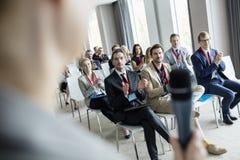Geschäftsleute, die für Öffentlichkeitssprecher während des Seminars in Konferenzzentrum applaudieren stockfotos
