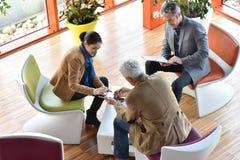 Geschäftsleute, die für eine Sitzung zusammentreten Stockfotografie