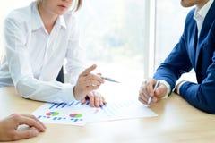 Geschäftsleute, die Finanzergebnisse auf Diagrammen um die Tabelle im modernen Büro analysieren Bunte Puppen auf schwarzem Hinter Lizenzfreies Stockfoto