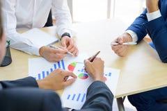 Geschäftsleute, die Finanzergebnisse auf Diagrammen um die Tabelle im modernen Büro analysieren Bunte Puppen auf schwarzem Hinter Lizenzfreie Stockfotos