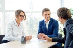 Geschäftsleute, die Finanzergebnisse auf Diagrammen um die Tabelle im modernen Büro analysieren Bunte Puppen auf schwarzem Hinter Lizenzfreies Stockbild
