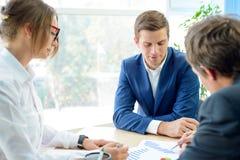 Geschäftsleute, die Finanzergebnisse auf Diagrammen um die Tabelle im modernen Büro analysieren Bunte Puppen auf schwarzem Hinter Lizenzfreie Stockbilder