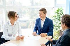 Geschäftsleute, die Finanzergebnisse um die Tabelle im modernen Büro analysieren Bunte Puppen auf schwarzem Hintergrund Stockfotos