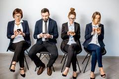 Geschäftsleute, die in Folge sitzen Stockfoto