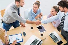 Geschäftsleute, die Hände über Tabelle rütteln stockbild