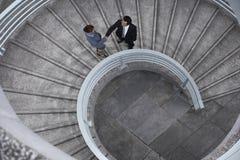 Geschäftsleute, die Hände auf Wendeltreppe rütteln Stockfoto