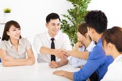 Geschäftsleute, die Hände bei einer Sitzung rütteln Stockfotografie