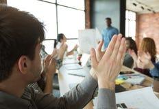Geschäftsleute, die Hände für Sprecher am Treffen klatschen lizenzfreies stockfoto