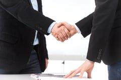 Geschäftsleute, die Hände im Büro rütteln Stockfotografie