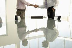 Geschäftsleute, die Hände im Konferenzsaal rütteln Stockfotografie
