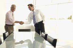 Geschäftsleute, die Hände im Konferenzsaal rütteln Lizenzfreies Stockbild