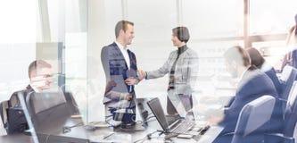 Geschäftsleute, die Hände in moder Planungs- und Führungsstab rütteln Stockfotos