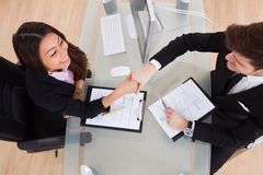 Geschäftsleute, die Hände am Schreibtisch rütteln Stockbilder