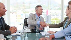 Geschäftsleute, die Hände während der Sitzung rütteln