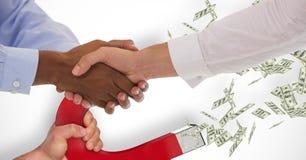 Geschäftsleute, die Hände während Magnet zieht Geld im Hintergrund rütteln stockbild