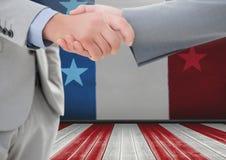 Geschäftsleute, die ihre Hände gegen amerikanische Flagge rütteln Stockfoto