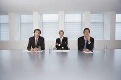 Geschäftsleute, die am Konferenztische sitzen Stockfoto