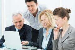 Geschäftsleute, die an Laptop arbeiten Stockfotos