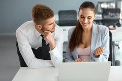Geschäftsleute, die Laptop-Computer bei Ofiice verwenden Lizenzfreie Stockfotos