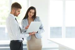 Geschäftsleute, die Laptop-Computer bei Ofiice verwenden Stockfotos