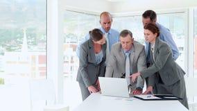 Geschäftsleute, die Laptop-Computer während der Sitzung betrachten stock footage