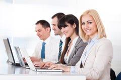 Geschäftsleute, die an Laptop im Büro arbeiten Stockbild