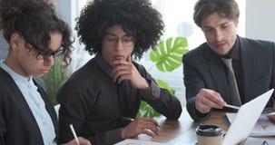 Geschäftsleute, die Laptop und Dokument bei der Bürositzung verwenden stock footage