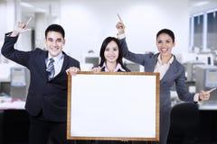 Geschäftsleute, die leeres Brett halten Stockfoto