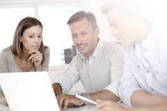 Geschäftsleute, die an Projekt mit Laptop arbeiten Stockfotos