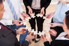 Geschäftsleute, die Puzzlen halten Stockfoto