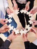 Geschäftsleute, die Puzzlen halten Lizenzfreies Stockfoto