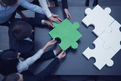 Geschäftsleute, die Puzzlespiel zusammenbauen Lizenzfreie Stockbilder