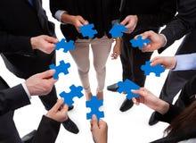 Geschäftsleute, die Puzzlespielstücke anschließen stockbild