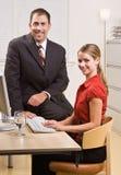 Geschäftsleute, die am Schreibtisch sitzen Stockbilder