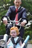 Geschäftsleute, die sein junges Kind zur Kinderkrippe reiten Lizenzfreie Stockfotografie