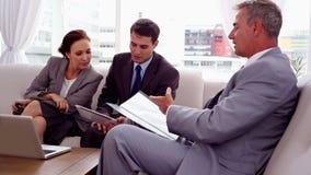 Geschäftsleute, die sich zusammen auf einer Couch besprechen stock video