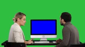 Geschäftsleute, die Sitzung um den Monitor über des Computers sprechend haben, was auf dem Schirm auf einem grünen Schirm ist, Fa stock video